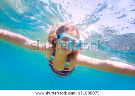 snorkeling blond kid girl underwater with goggles and swimsuit in Mediterranean sea - stock photo