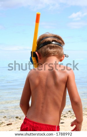 Snorkeling boy on the beach, from behind - stock photo