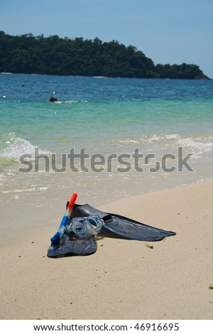 Snorkeling equipment (mask, snorkel and fins) on white sand beach with ocean on background