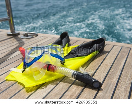 Snorkeling equipment on the wooden deck of a private luxury motor yacht traveling on tropical ocean - stock photo
