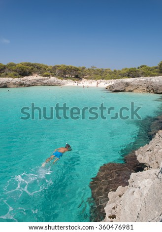 Snorkeling in a beautiful cala in Minorca, cala Talaier, Balearic islands, Spain. - stock photo
