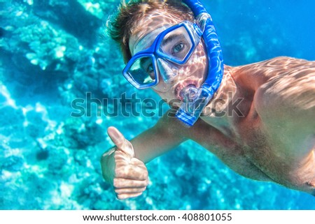 Snorkeling man underwater giving thumbs up ok signal wearing snorkel and mask having fun on beach summer holidays vacation enjoying recreational leisure time swimming in the sea. - stock photo