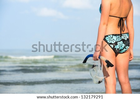 Snorkeling or diving, silhouette of hand with equipment for snorkeling, on the beach (picture with space for text) - stock photo