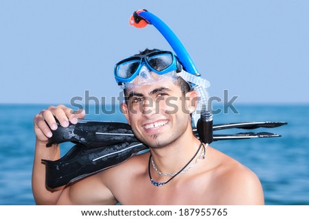 snorkler resting on shore with his diving equipment - stock photo