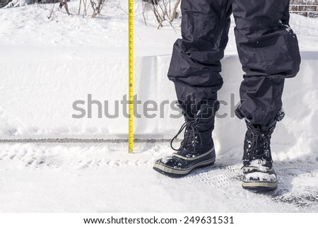 Snow Accumulation is Measured with a Yellow Tape - stock photo