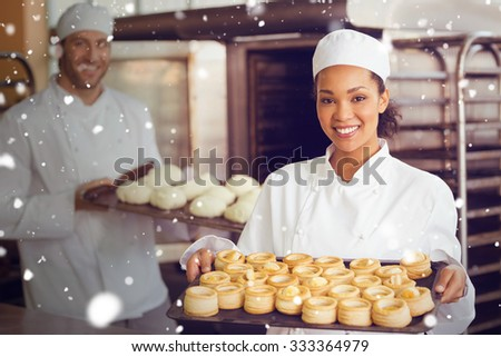Snow against baker smiling at the camera holding tray - stock photo