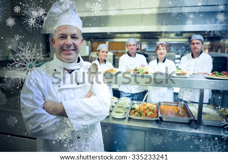 Snow against experienced head chef posing proudly in a modern kitchen - stock photo