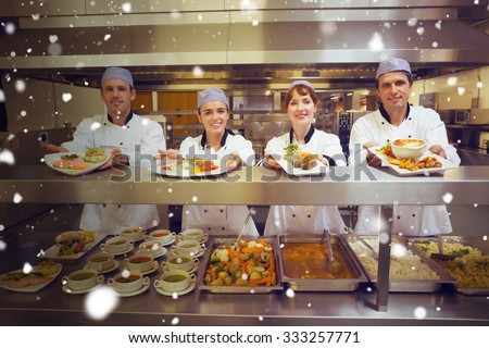 Snow against four young chefs showing plates - stock photo