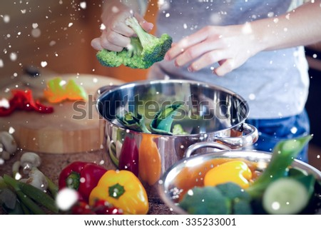 Snow against woman preparing healthy dinner - stock photo