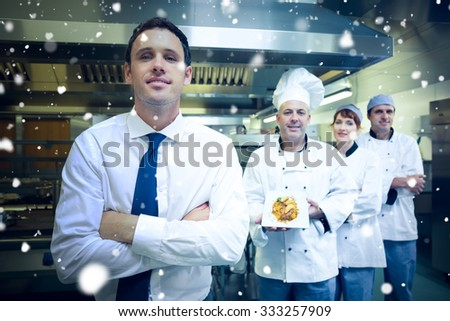 Snow against young restaurant manager posing in front of team of chefs - stock photo