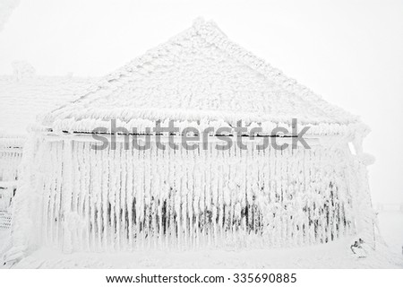 Snow and ice covered house after blizzard at winter - stock photo