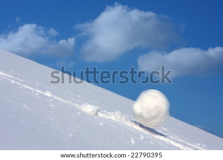 Snow ball slides downhill and speeds up. - stock photo