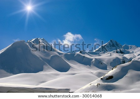Snow-bound mountain peaks, bright sun and clouds - stock photo