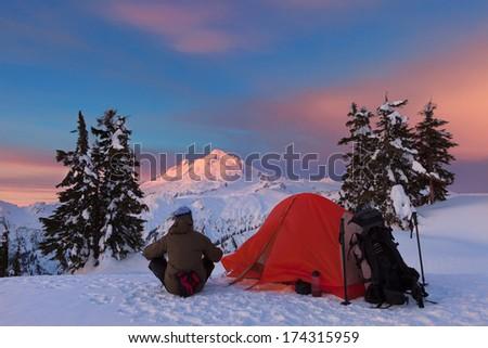 Snow Camper Enjoying Sunrise Glow on Snow Peak - stock photo