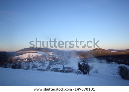 snow cannons at willingen in evening light - stock photo