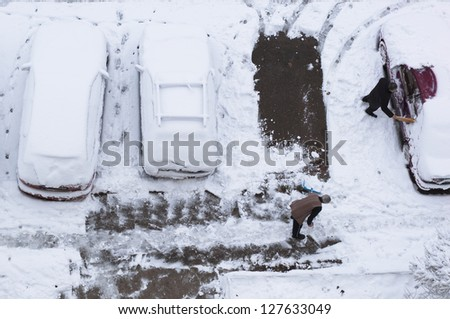 Snow capped cars in parking area, Men cleaning the snow - stock photo
