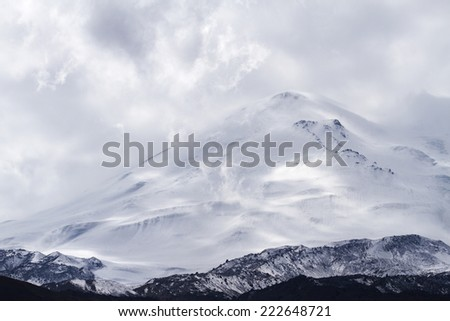 Snow-capped Elbrus mountain surrounded by clouds rises above the mountain area in Kabardino-Balkaria (Caucasus, Russia). Can be used as a background, wallpaper or postcard.