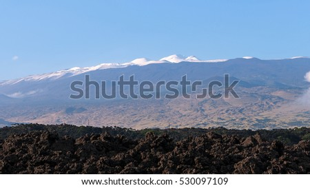 Snow-capped Mauna Kea as seen from Saddle Road with a lava field in the foreground