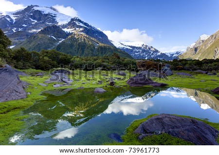 Snow capped mountain peaks are reflected in a small pool - stock photo