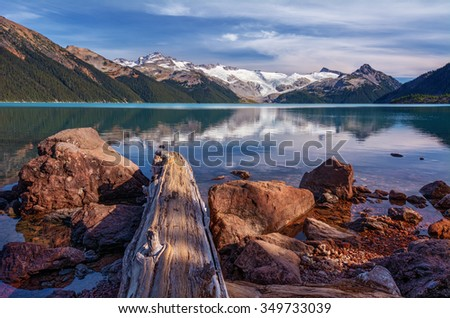 Snow-capped mountains, calm glacial lake, rocks and log on the foreground - stock photo