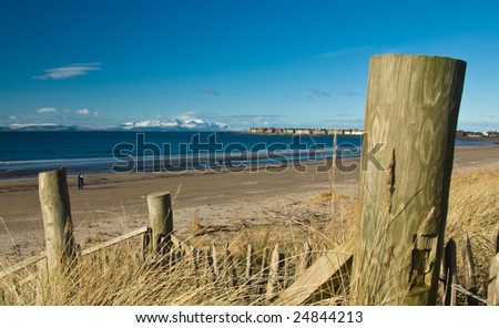 Snow-capped mountains on Island of Arran viewed from Troon beach, Ayrshire, Scotland, UK - stock photo