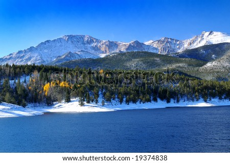 Snow capped Pikes Peak at Crystal Reservoir with a touch of golden aspen trees - stock photo