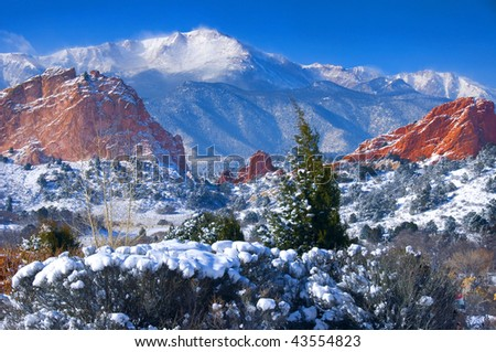 Snow capped Pikes Peak soaring over the Garden of the Gods Park after a fresh snowfall - stock photo