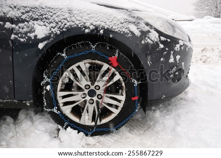 snow chain on the wheel of a car in bad weather conditions - stock photo