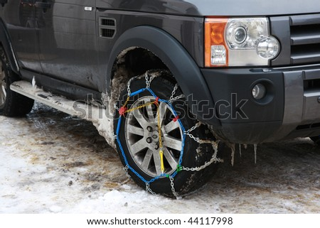 Snow chains fitted to a 4x4 car. - stock photo