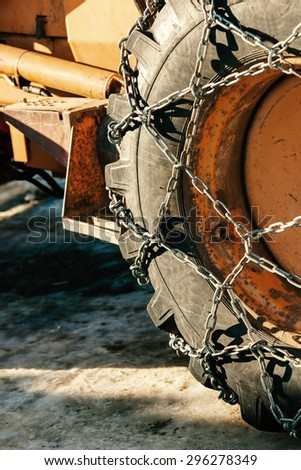 Snow chains outside of a tractor tire - winter transportation image winter - stock photo