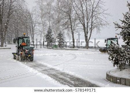 Snow cleaning buses in town during heavy snowfall