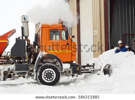 Snow cleaning on industrial area by means of the truck. - stock photo