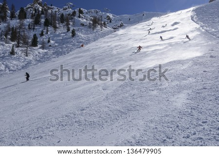 snow clouds on steep ski run #2, Arabba; skiers lift steamy clouds of snow descending steep slope in Dolomites, shot in back-light - stock photo