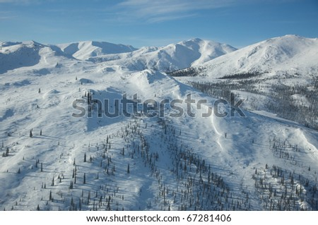 Snow covered Alaskan mountains under a blue sky.