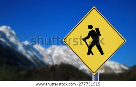 Snow covered Alps with hiker symbol on yellow traffic road label - stock photo