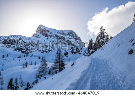 Snow-covered altitude mountain road winding in the Dolomites, Italian Alps at sunset
