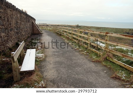 snow covered bench on the ballybunion cliffside walk in winter - stock photo