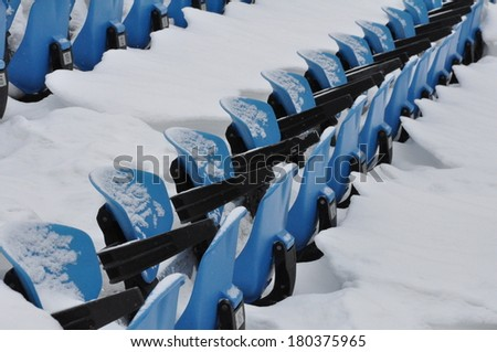 Snow-covered blue plastic folding seats lined up in the Olympic park in Montreal, Quebec - stock photo