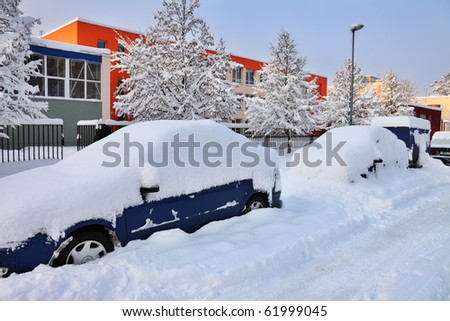 snow-covered car lot in town - stock photo