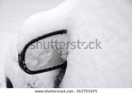 snow covered car with only side view mirror out - stock photo