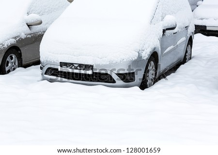 Snow covered cars after snowfall - stock photo