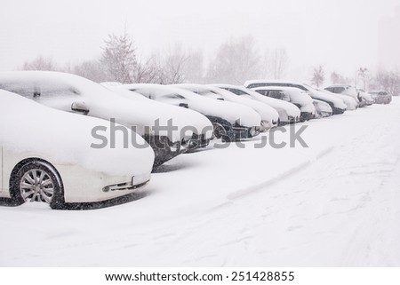 Snow-covered cars during a winter blizzard  - stock photo
