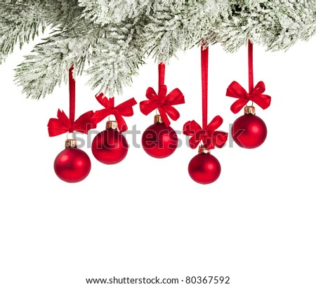 Snow covered Christmas branch with red balls on white - stock photo