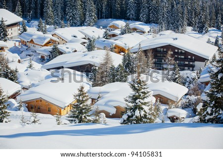 Snow-covered cottages at the Austrian Alps of the Tyrol region. - stock photo