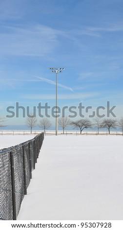 Snow covered empty baseball field in Chicago Illinois Lake Michigan Beachfront Park - stock photo