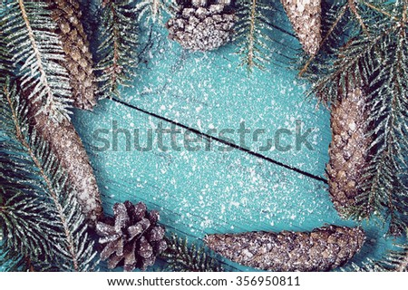 Snow-covered fir branches and fir cones on a green wooden background - stock photo