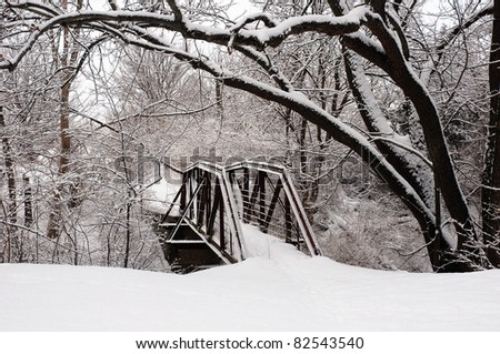Snow Covered Foot Bridge in Wooded Park - stock photo