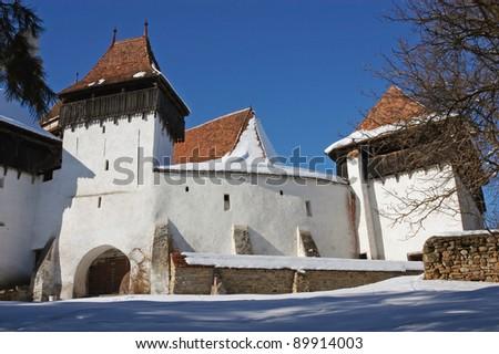 Snow covered fortified church of Viscri (Weisskirch, Szaszfeheregyhaza) at wintertime in Transylvania, Romania. UNESCO heritage - stock photo