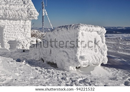 Snow covered, frozen car at winter near a meteorological station