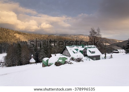 Snow covered house during sunset in a frosty mountains country in winter evening - stock photo